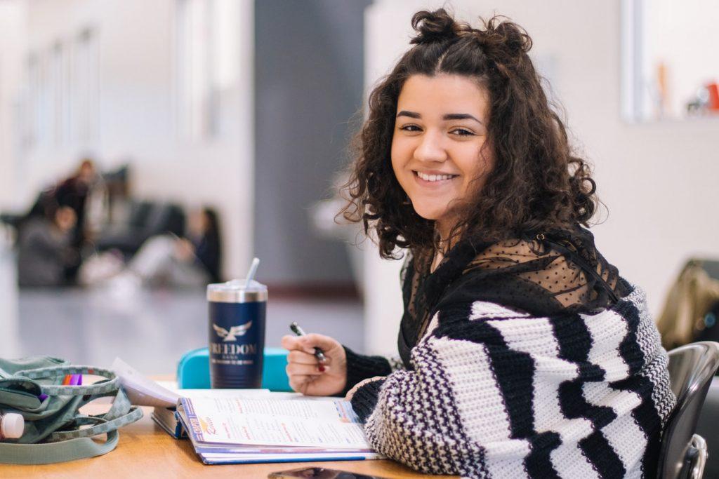 girl smiling while writing
